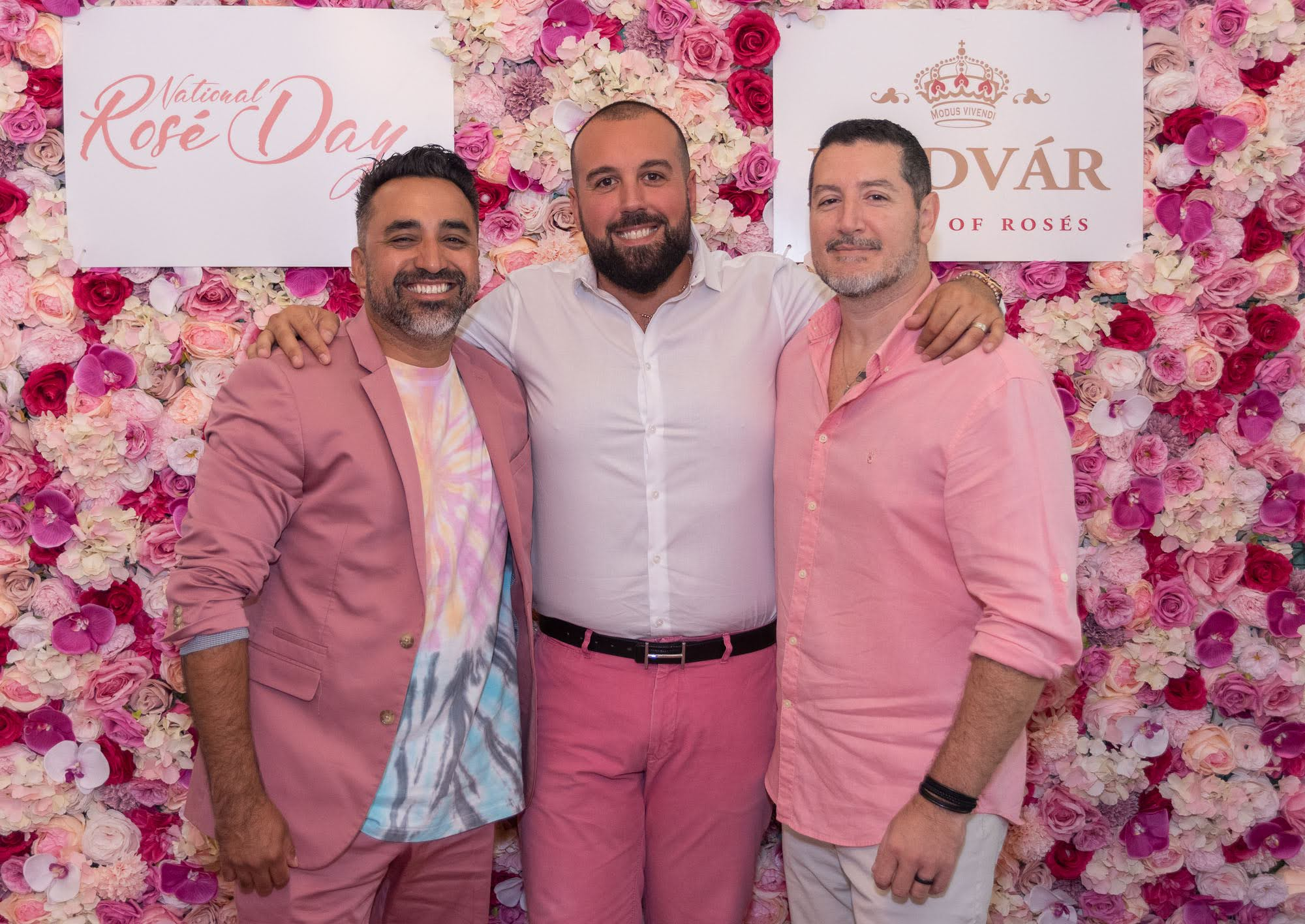 Three gentlemen posing for a photo in front of a floral wall